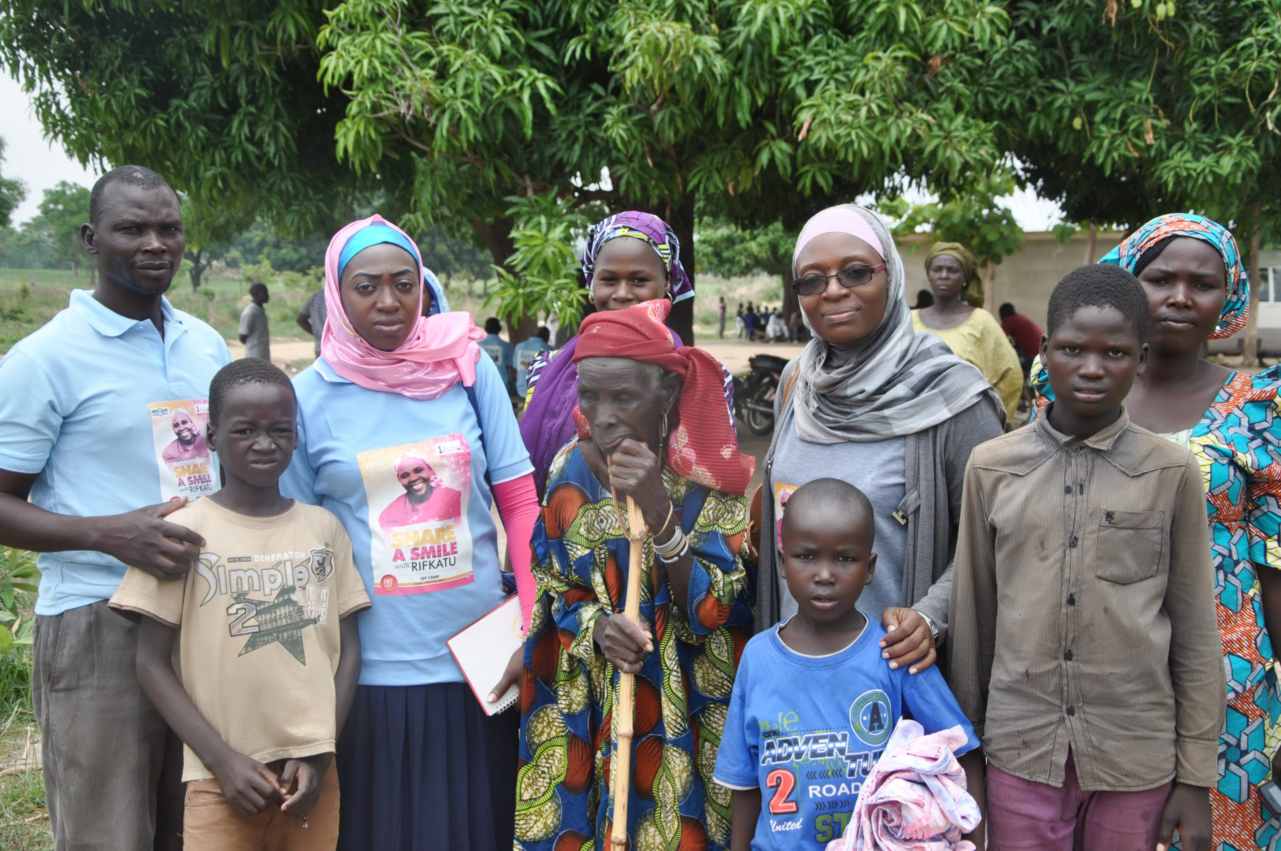 FCT State Project Lead with an elderly woman and her grand children in the camp